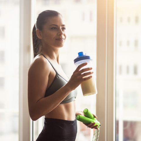 young female athlete drinking protein shake after workout