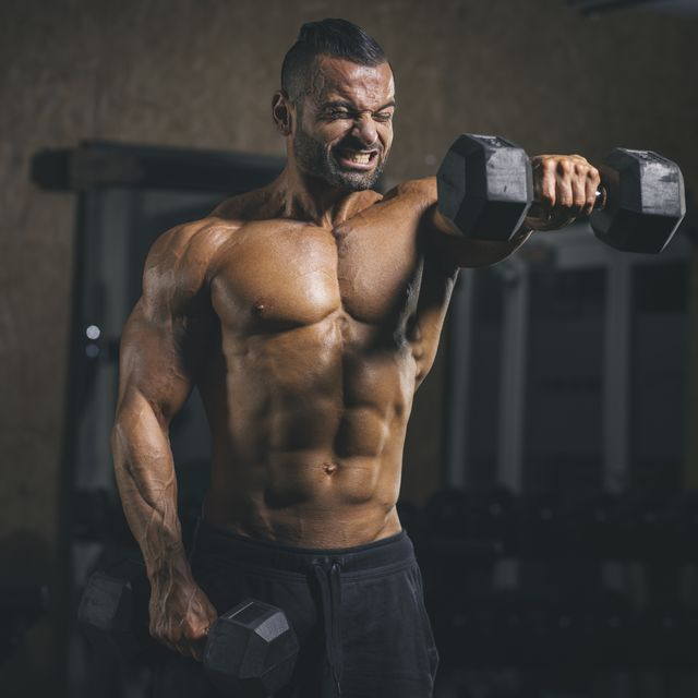 bodybuilder performing dumbbell front raises in his shoulder workout in gym