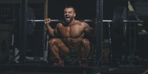 Gespierde man zonder shirt voert heel veel zwaresquats uit voor German Volume Training.