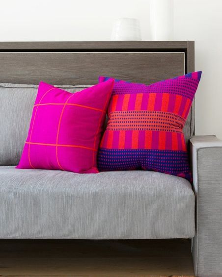 neon pink throw pillows on grey couch