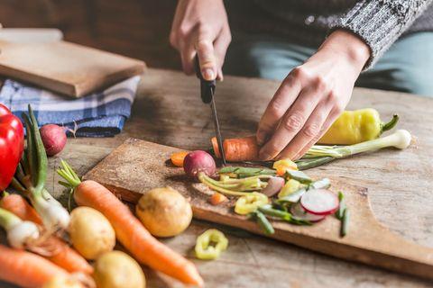 Een vrouw die groente snijdt op een houten snijplank.