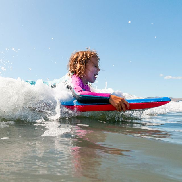 young girl boogie boarding in ocean
