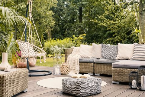 book on a black and white pouf in the middle of a bright terrace with a rattan corner sofa, hanging chair and round rug real photo