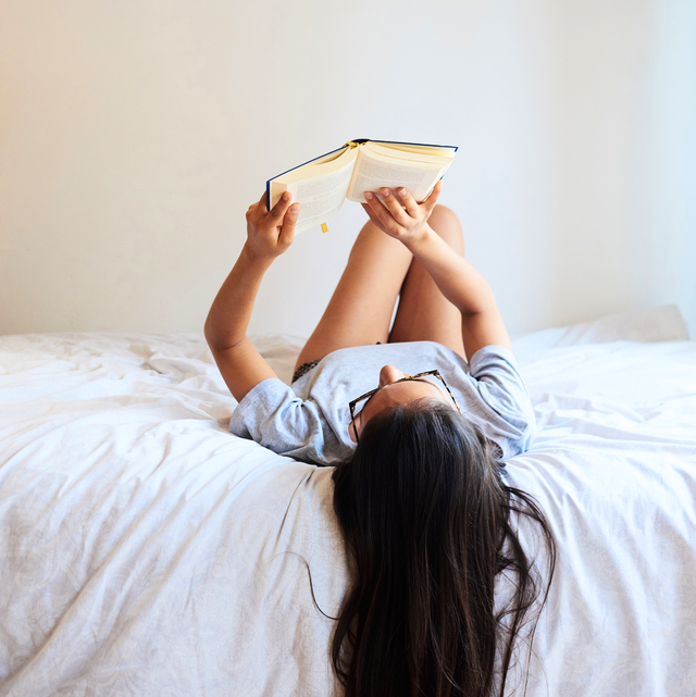 beautiful pretty woman in glasses lying with novel on bed at home