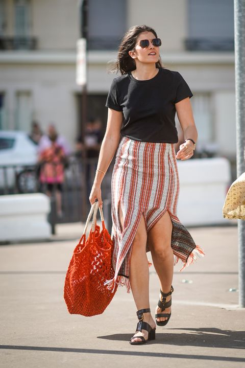 paris, france   june 30 a guest wears sunglasses, a black top, a white and red striped and fringed skirt, a woven red shopping bag, black ankle strap sandals, outside acne, during paris fashion week   haute couture fallwinter 20192020, on june 30, 2019 in paris, france photo by edward berthelotgetty images