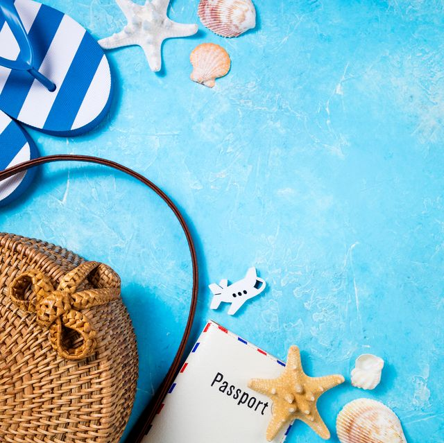 Summer female fashion beach accessories flip flop, bamboo bag and passport on blue background. Journey, vocations, travel and summer rest concept