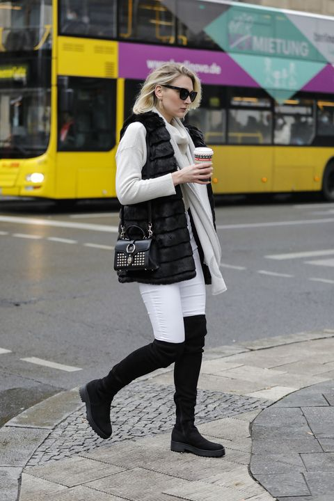 berlin, germany   december 11 german model and actress victoria jancke wearing a black faux fur vest by karl lagerfeld, a beige cashmere scarf by gucci, a cream colored turtleneck pullover by vero moda, a black bag with gold studs by aigner, white pants by top shop, black wide fit platform overknee boots by evenodd, gold earrings by lea y paola and black sunglasses by pilgrim during a street style shooting on december 11, 2020 in berlin, germany photo by streetstyleshootersgetty images