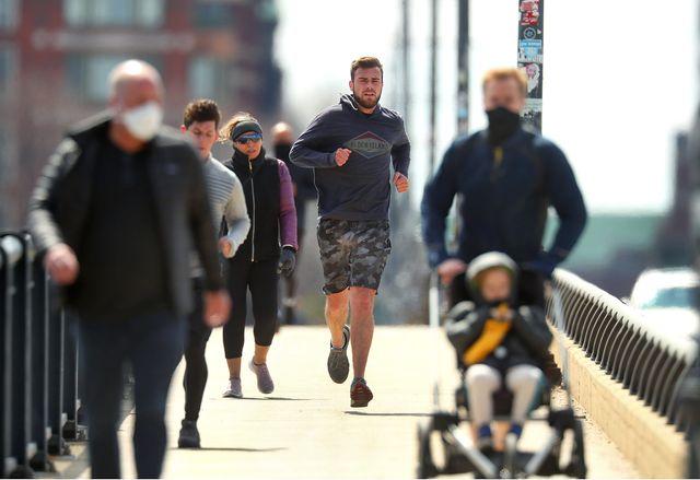 un corredor sin mascarilla adelanta a otros paseantes con ella en el paseo marítimo de melilla