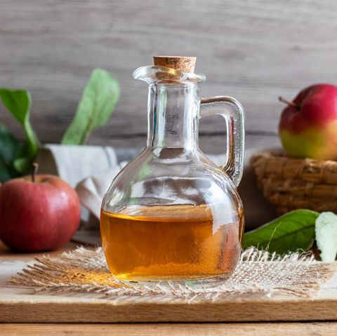 Une bouteille de vinaigre de cidre avec des pommes fraîches