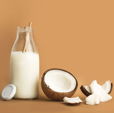 a bottle of coconut milk and pieces of coconut