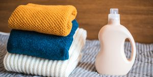 Bottle of detergent next to a pile of sweaters - how to clean jumpers.