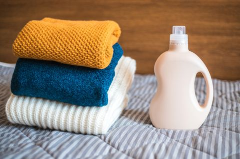 Bottle of detergent and a pile of sweaters.