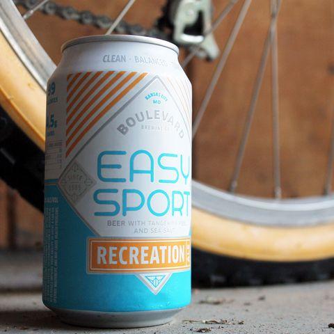 Bicycle wheel rim, Aluminum can, Bicycle tire, Rim, Beverage can, Tin can, Spoke, Automotive tire, Logo, Orange,