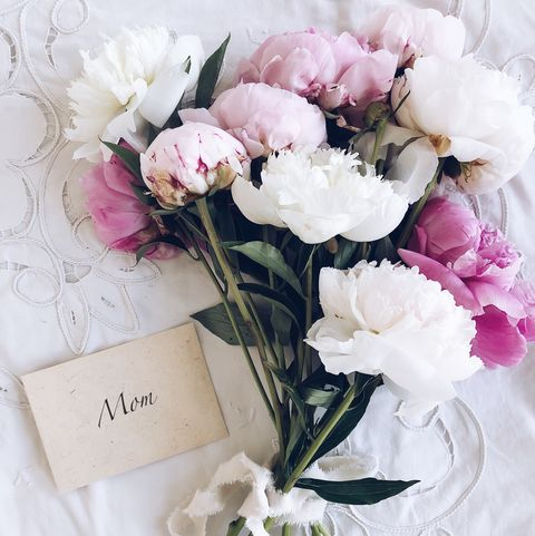 Bouquet of peonies next to an envelope with the word mom