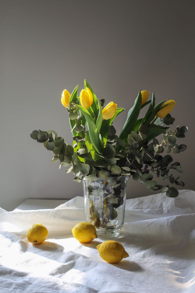 bouquet of yellow tulips in glass vase on table