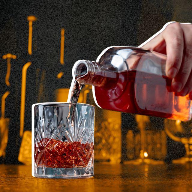 a hand pouring bourbon