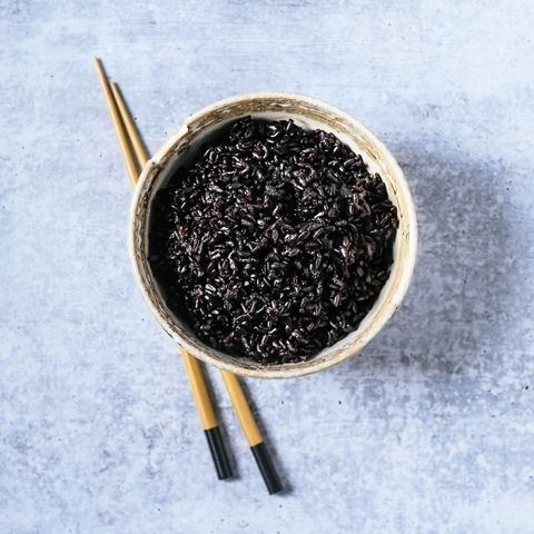 bowl of black rice with chopsticks on blue background