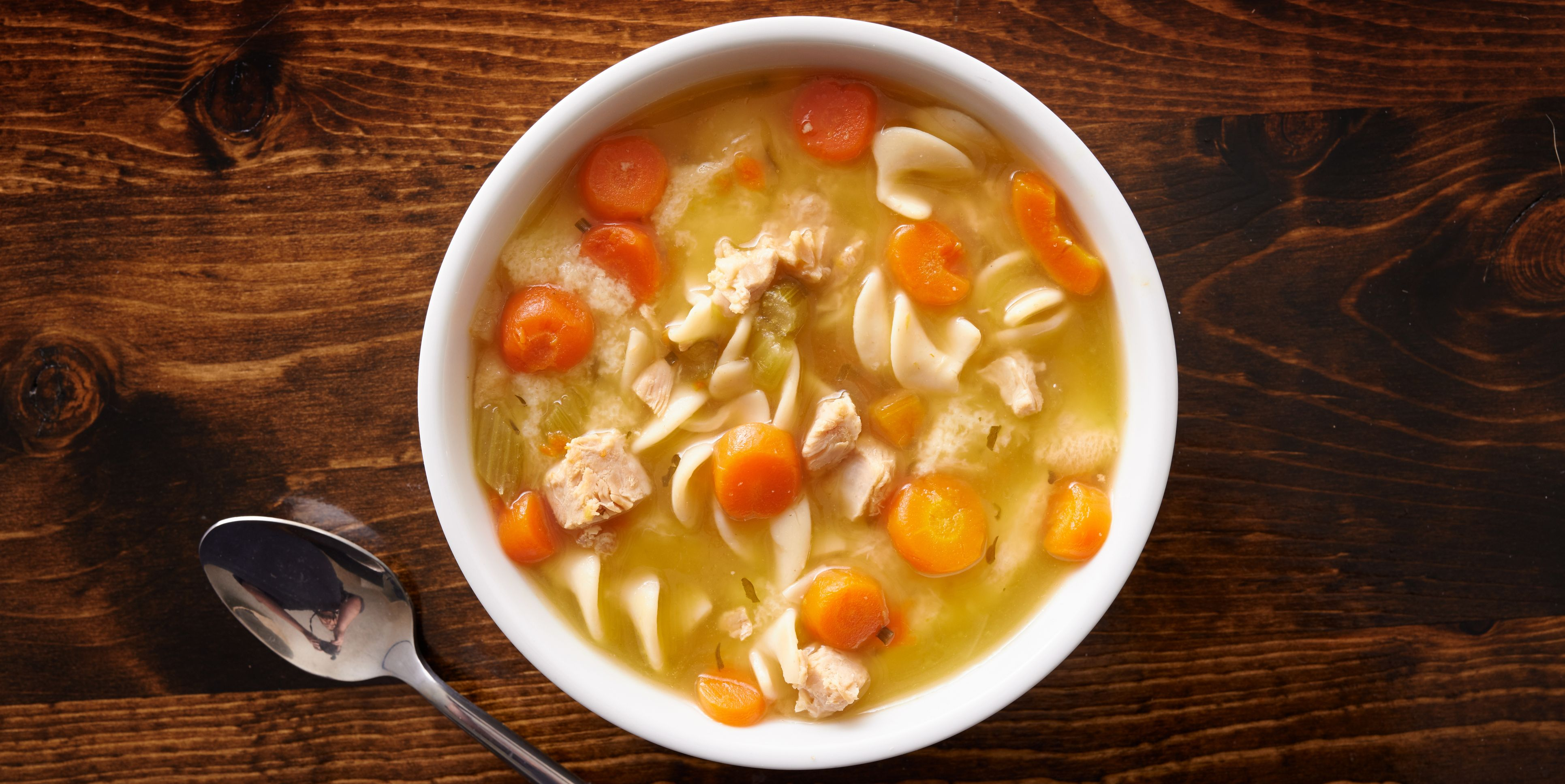 bowl of chicken noodle soup shot top down