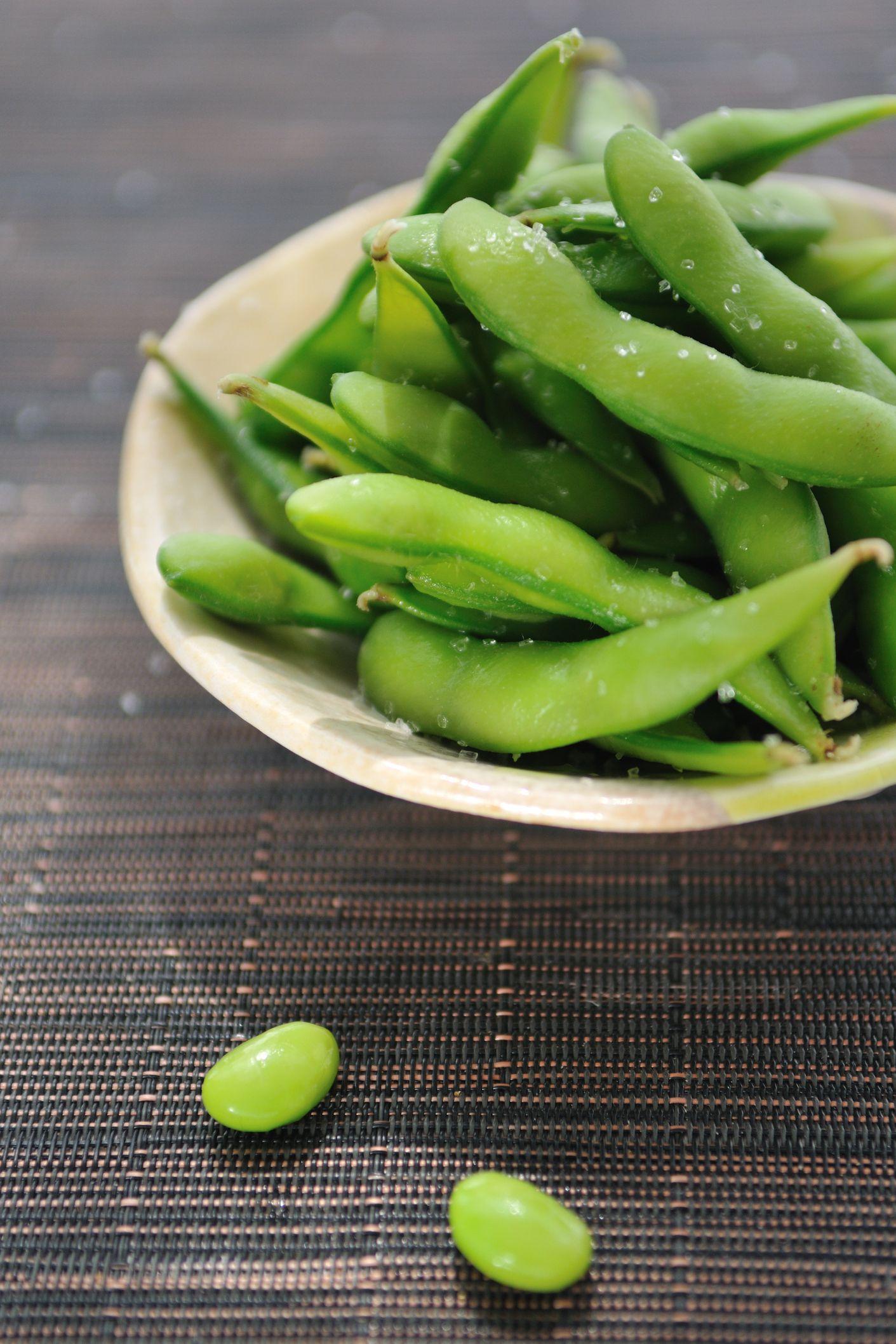 Bowl of edamame beans on bamboo mat