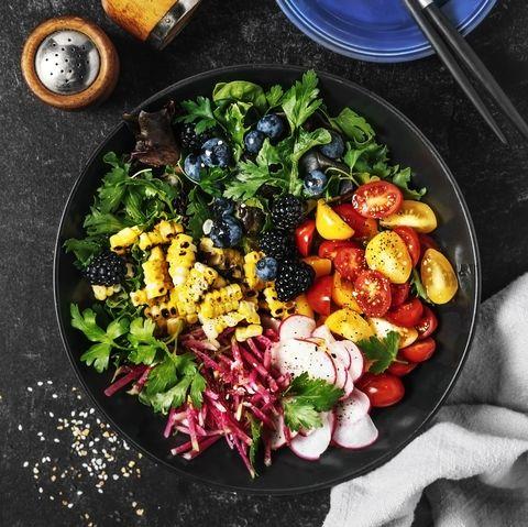bowl of fresh salad on black background