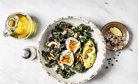 Bowl of kale salad with boiled eggs and avocado on white background