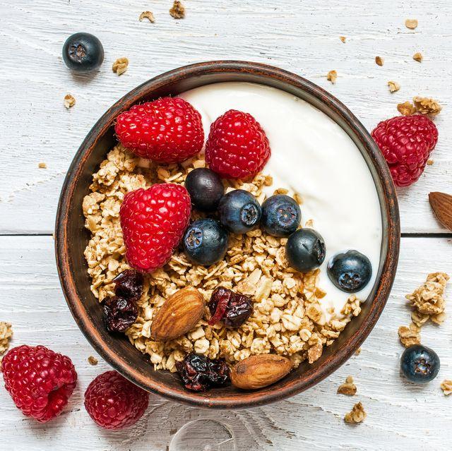 bowl of oat granola with yogurt, fresh raspberries, blueberries