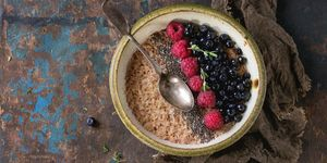 Bowl of oatmeal porridge with blueberries, raspberries and chia seeds, served with sackcloth rag and vintage spoon over old wood textured background. Rustic breakfast theme. Top view, space for text