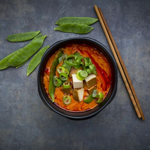 Bowl of red Thai Curry with snow peas, carrots, bell pepper, spring onions and smoked tofu