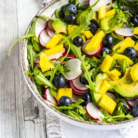 bowl of rocket salad with mango, avocado, red radishes and blueberries
