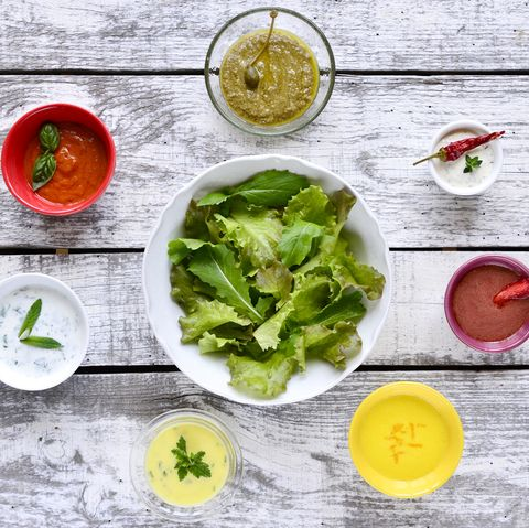 bowl of salad leaves with various salad dressings