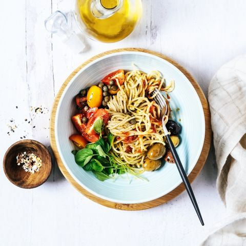 bowl of spaghetti with basil, tomatoes and olives on white, wooden background