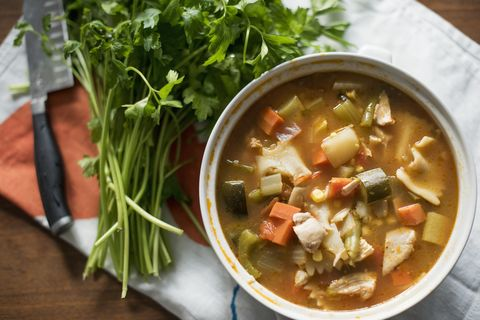 a bowl of vegetable stew and a bunch of fresh herbs on a table