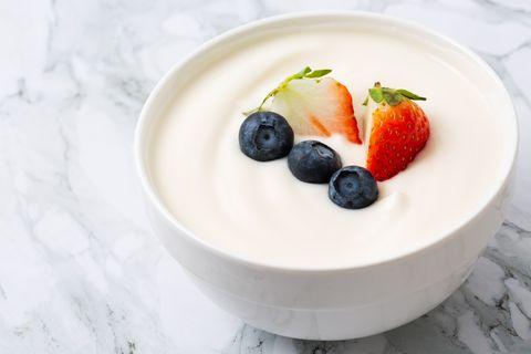 bowl of yogurt and fresh berries on white fresh yogurt, strawberries, blueberries, handmade