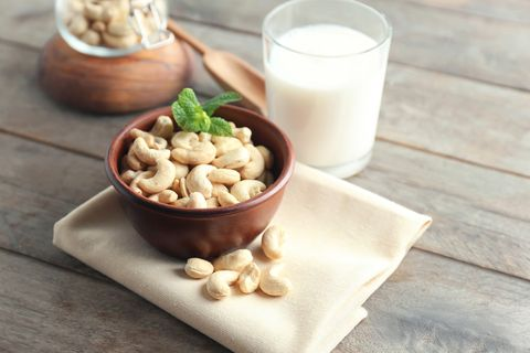 Bowl with tasty cashew nuts and glass of milk on table