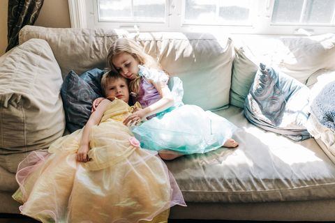 a boy and girl dressed in princess dresses sit on a couch