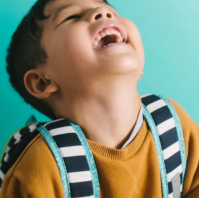 boy laughing with a striped backpack