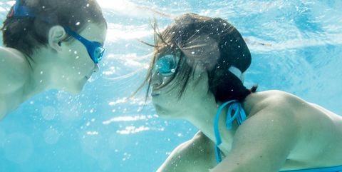 Boy diving underwater with his mum, swimming pool