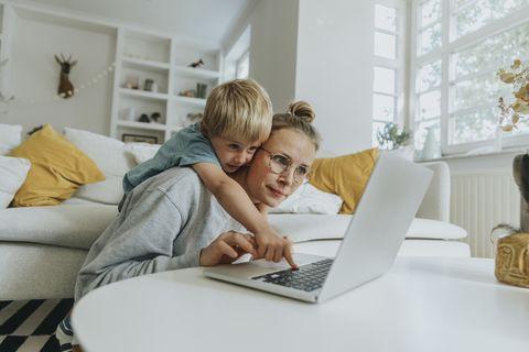 en el salón de casa, una madre intenta consultar su portátil mientras su hijo se sube a ella y la interrumpe