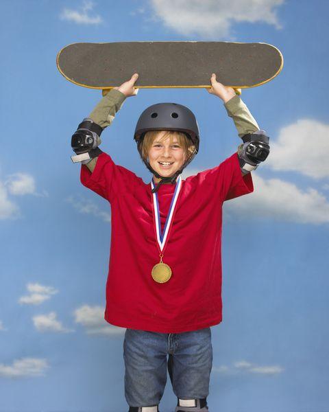 boy holding skateboard overhead