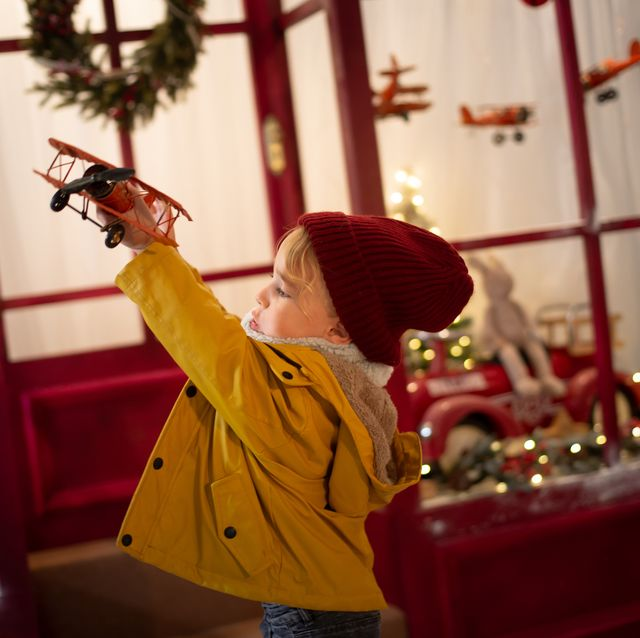 boy making a plane fly in front of a christmas toy store