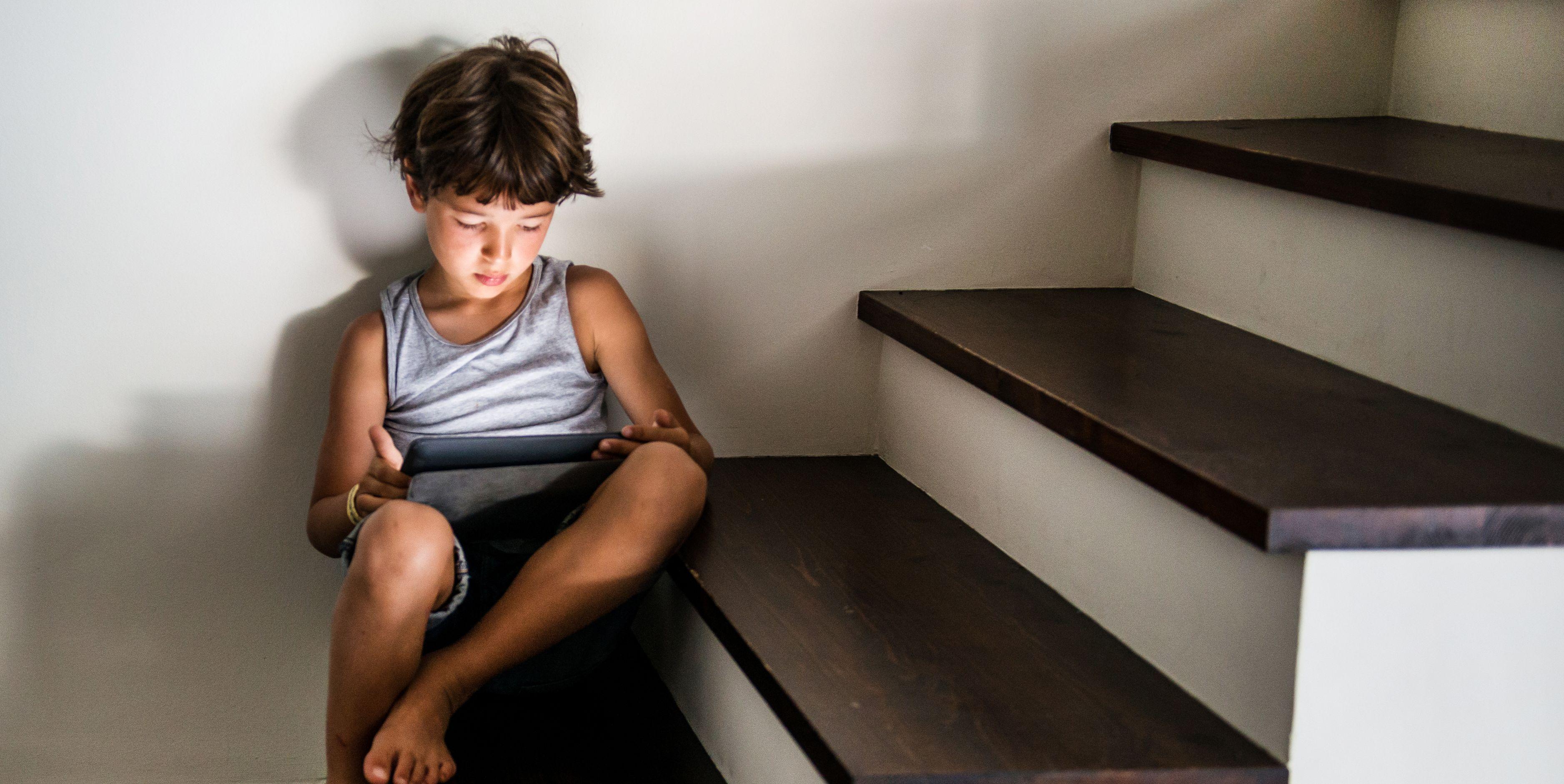 Niño jugando con tablet sentado en escaleras