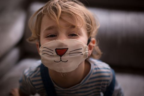 boy wearing a surgical mask painted as a cat
