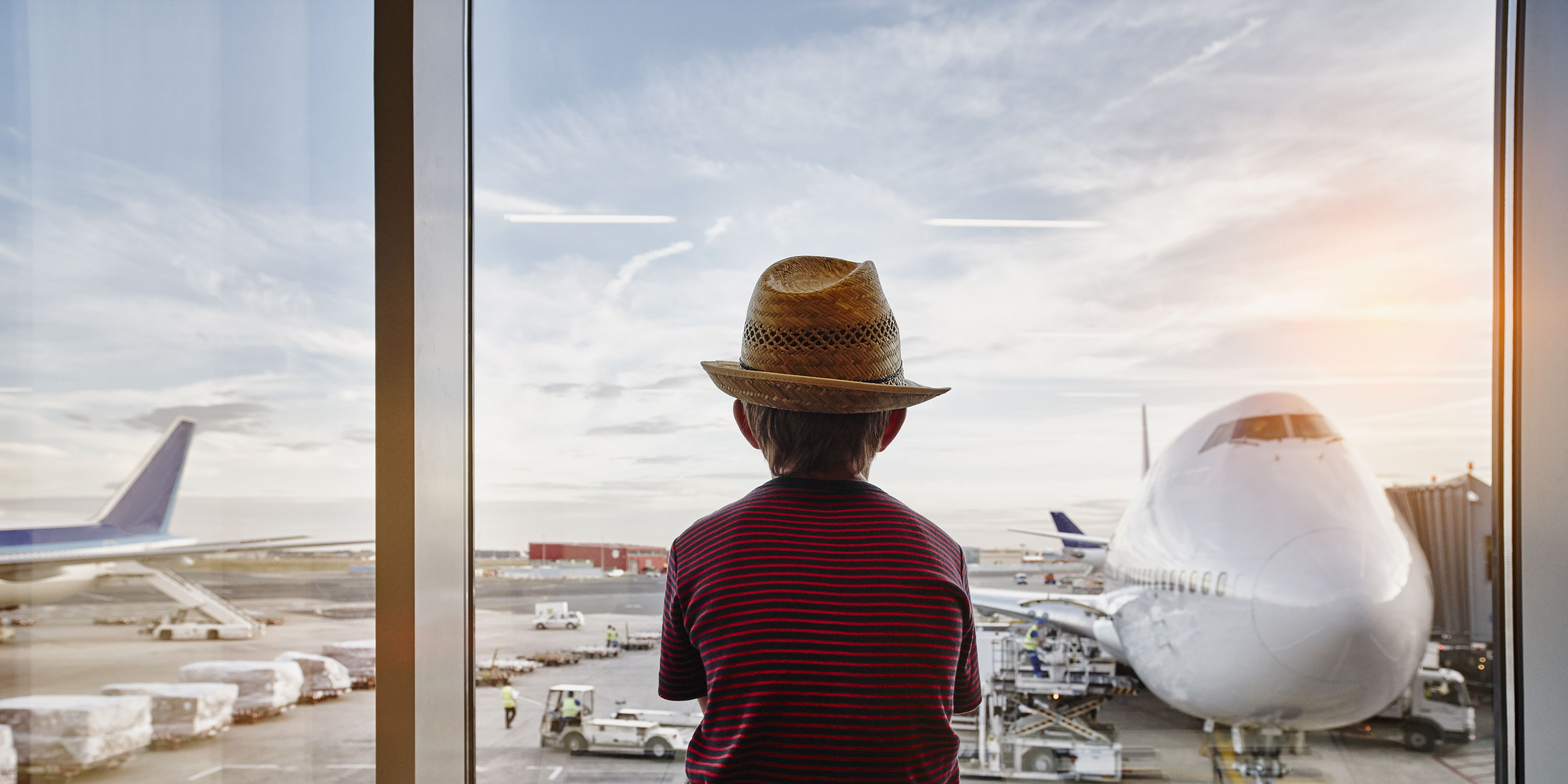 Boy wearing straw hat looking through window to airplane on the apron