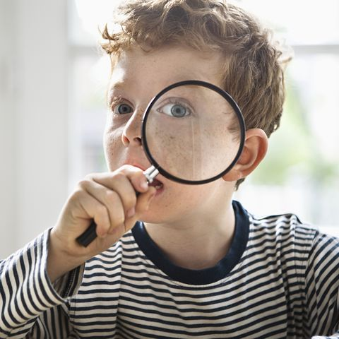 boy 7 9 with magnifying glass