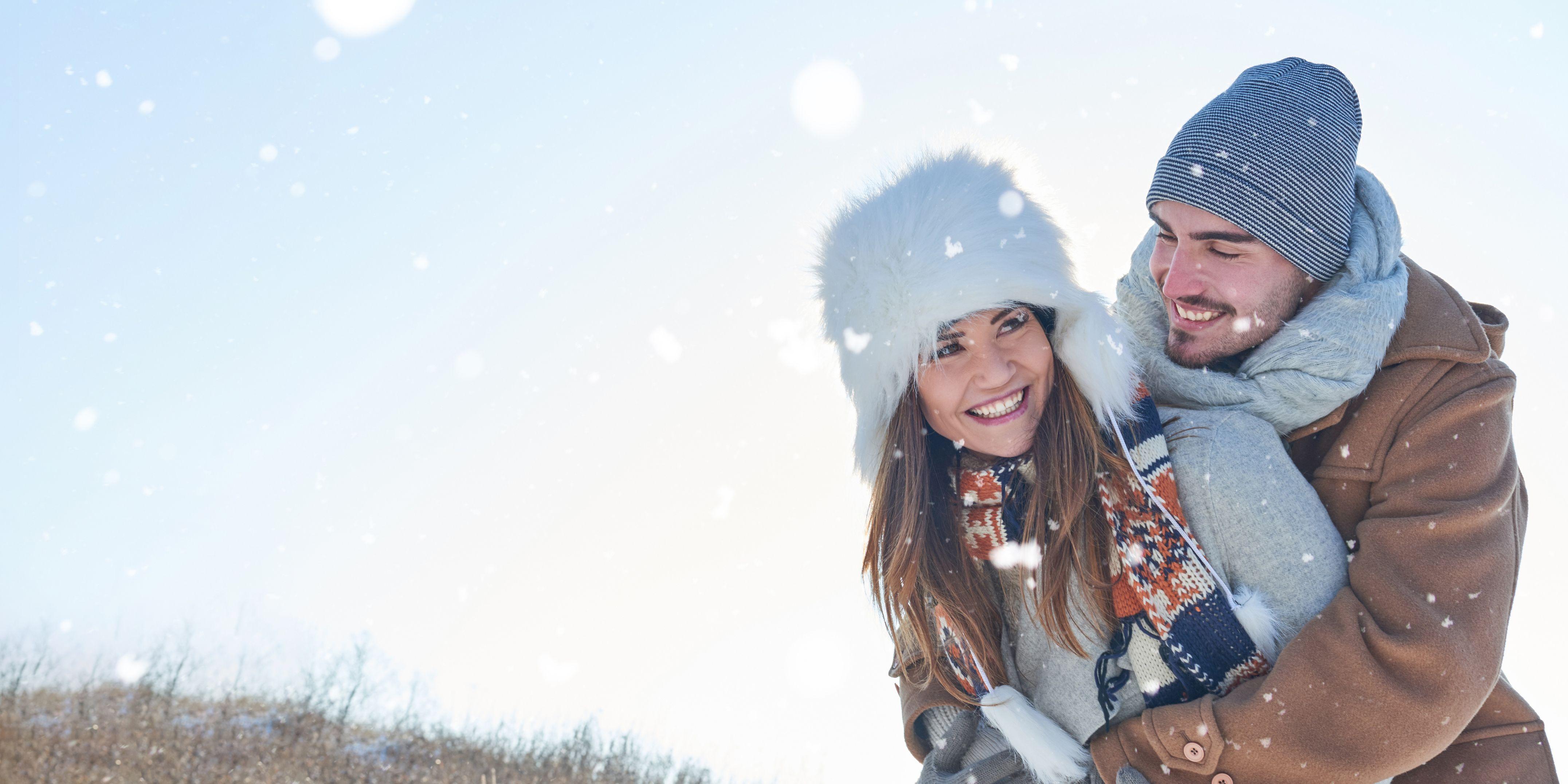 Boyfriend Embracing Cheerful Girlfriend Against Clear Sky During Snowfall