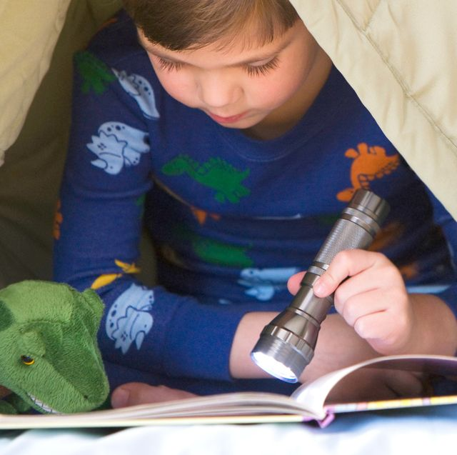 boy in dinosaur pajamas reading a book under the blanket