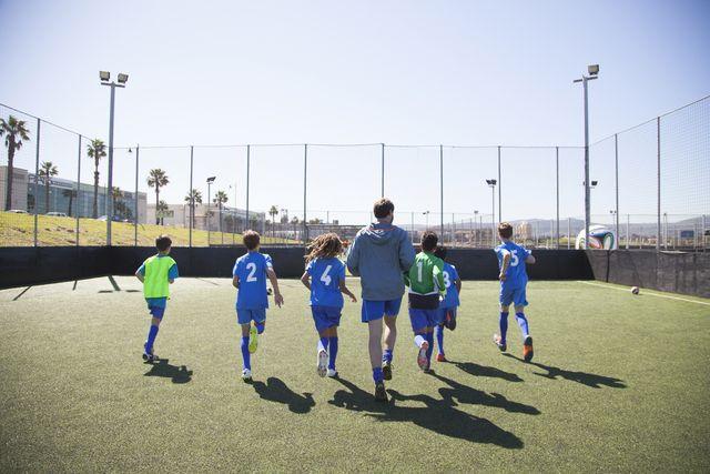 un grupo de niños futbolistas calienta para un partido con la supervisión de su entrenador