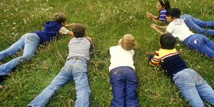 Children laying on grass picking dandelions,Santa Fe National Forest, NM
