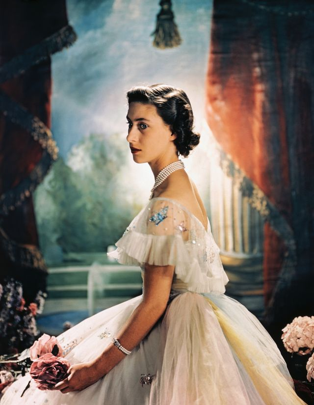 original caption princess margaret rose of england, is shown here seated and wearing a formal evening dress with sequence butterflies around the shoulder, and holding two pink roses
