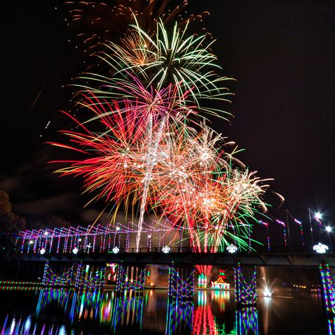 fireworks bursting over river with bridge lighted below it in christmas lights